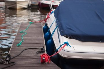 A dock with the end of a small boat tied to it. The boat has a tarp over it.
